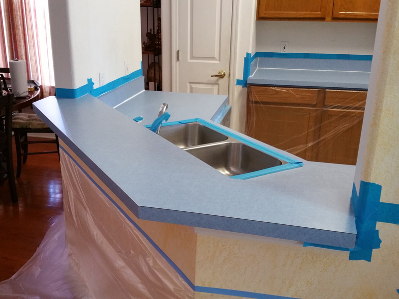 an ugly blue color kitchen countertop being prepared for refinishing