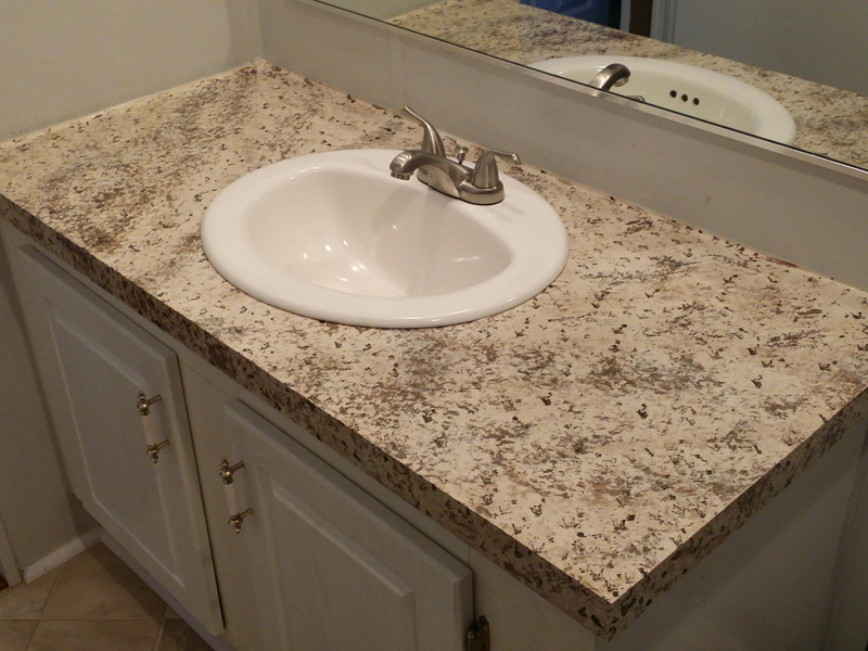 A bathroom countertop looks like granite pink and brown color.