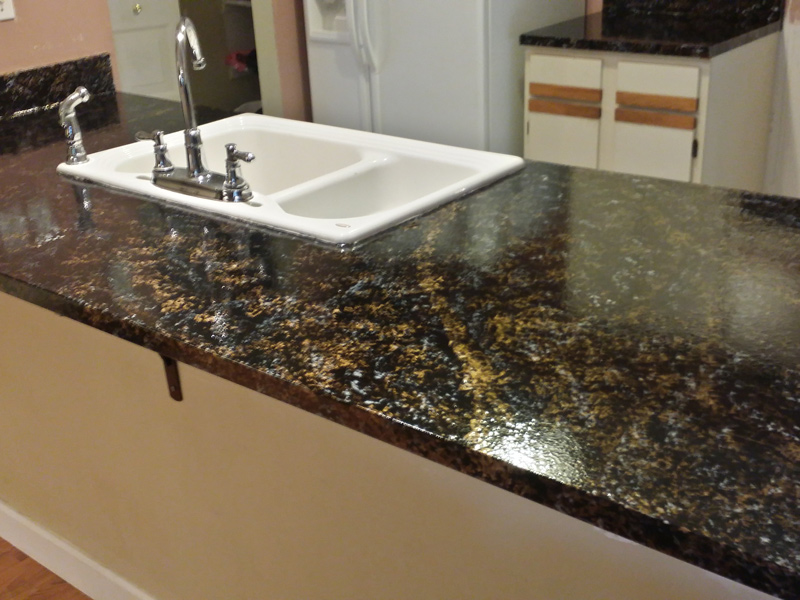 the same large kitchen countertoop after refinishing with granite countertop overlay